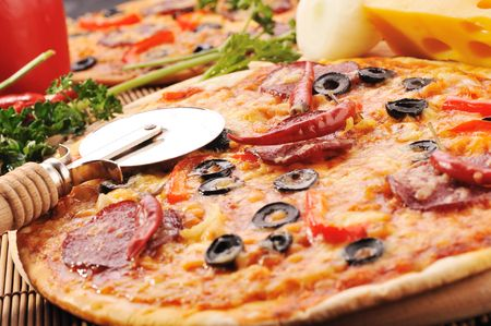 Close up of  pizza with tomatoes, cheese, black olives and  peppers.
