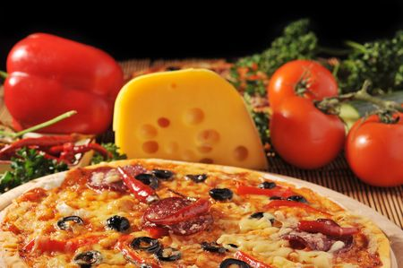 color photography: Close up of  pizza with tomatoes, cheese, black olives and  peppers.