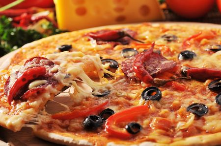 Close up of  pizza with tomatoes, cheese, black olives and  peppers. photo