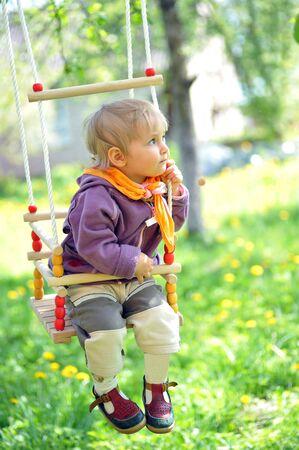 Swinging little girl in park photo