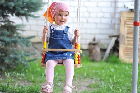 Swinging little girl in park