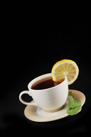 full cup of tea with lemon and  greens  leaves on  black Stock Photo - 6404422