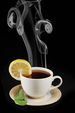 full cup of tea with lemon and  greens  leaves on  black Stock Photo - 6404466