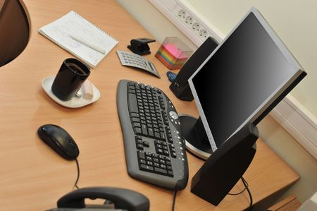 Workplace in office with monitor  and cup on work table photo