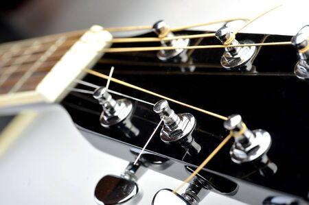 Details of  acoustic black guitar. neck, nut, frets, strings. photo