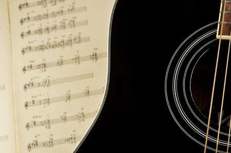 Acoustic guitar laying across sheet music photo