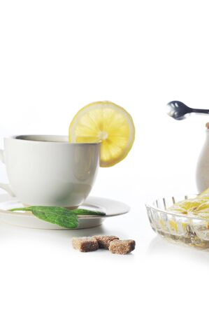 full cup of tea with lemon and greens leaves  photo