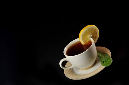 full cup of tea with lemon and  greens  leaves on  black Stock Photo - 6412193