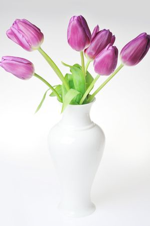 bouquet of many violet tulips in  porcelain vase photo