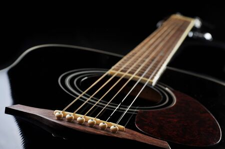 acoustic guitar: Detail of an acoustic black guitar with the strings and the sound hole Stock Photo