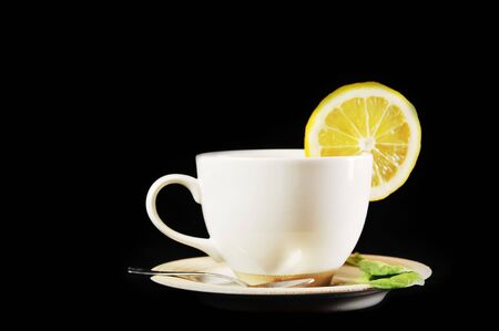 full cup of tea with lemon and  greens  leaves on  black Stock Photo - 6492062