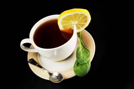 full cup of tea with lemon and  greens  leaves on  black Stock Photo - 6492087