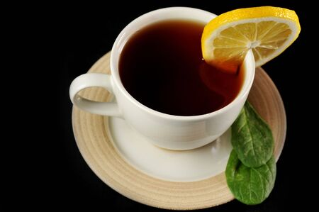full cup of tea with lemon and  greens  leaves on  black Stock Photo - 6492210