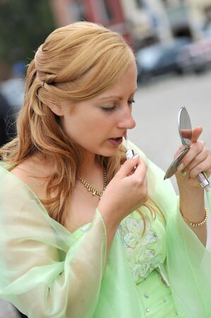 woman applying make up using small mirror Stock Photo - 6548693