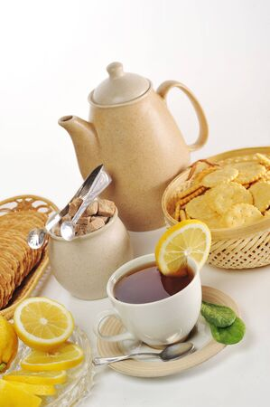cup of tea with lemon  and  cookies in  basket photo