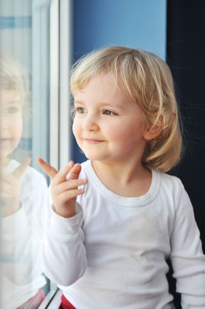 look through window:  cheerful little girl sits at  window portrait
