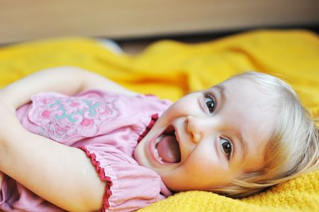 family with one child: Beautiful little girl  lying on  bed at  house Stock Photo
