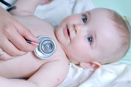 doctor exams baby with stethoscope photo