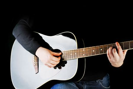 Young man playing on black  guitar. photo