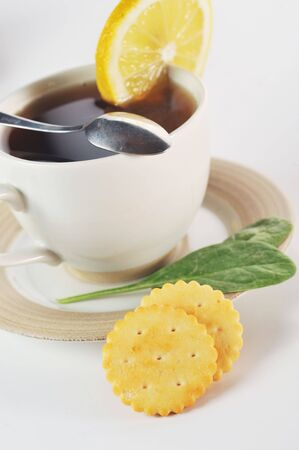 full cup of tea with lemon and  pastry photo