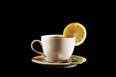 full cup of tea with lemon and  greens  leaves on  black Stock Photo - 6600760