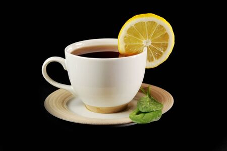 full cup of tea with lemon and  greens  leaves on  black Stock Photo - 6599581