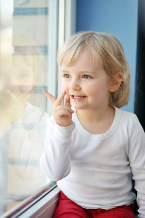 cheerful little girl sits at  window portrait Stock Photo - 6625497