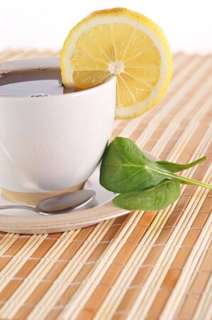 On  wooden napkin full cup of tea with lemon photo