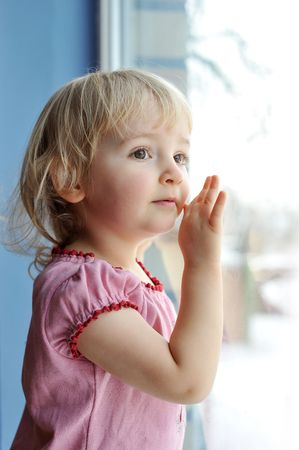 only: thoughtful little girl is by window portrait