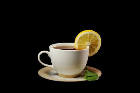full cup of tea with lemon and  greens  leaves on  black Stock Photo - 6682510
