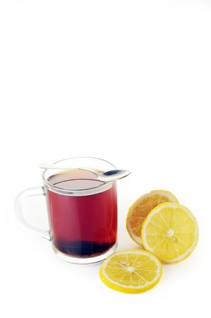 Full glass cup of tea and  lemon close up  photo
