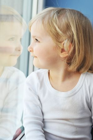 cheerful little girl sits at  window portrait photo