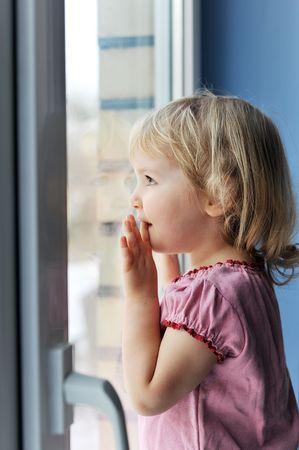 thoughtful little girl is by window portrait photo