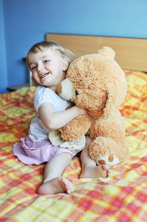 cheerful little girl with soft  toy sits on bed of parents photo