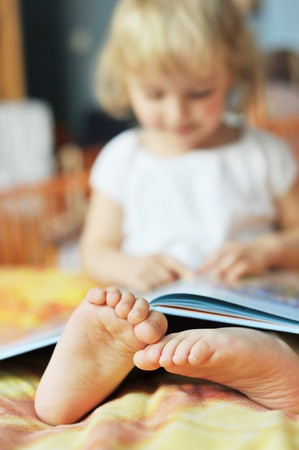cheerful little girl with book sits on bed of parents photo