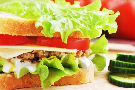 sandwich with  cutlet and vegetables lies on  plate photo