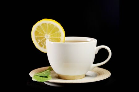 full cup of tea with lemon and  greens  leaves on  black Stock Photo - 7128517