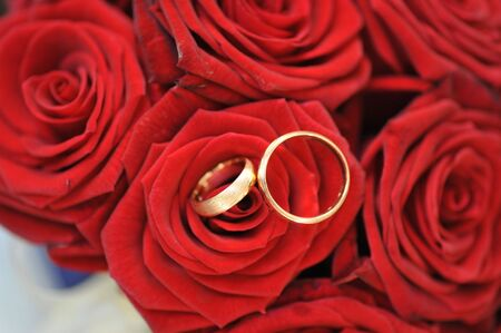 bouquet of red roses and wedding gold rings photo