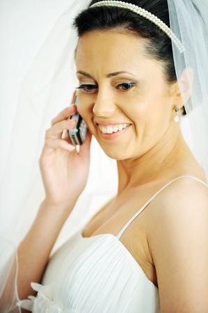 beautiful stylish bride speaks on  phone. Studio portrait photo