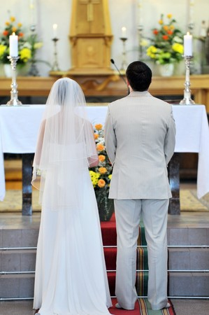 Wedding ceremonies in  church.  groom and  bride photo