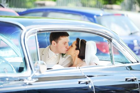 newlywed couple, groom  and bride,  kissing in car photo