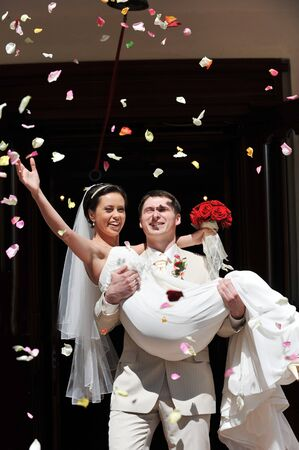 marriage ceremony: Newly wed couple being showered in rose petals Stock Photo