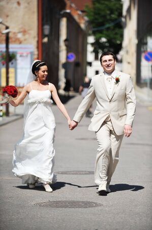 Newly wed couple  run on sidewalk Stock Photo - 7318939