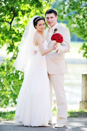 groom and bride in white dress on background of green trees Stock Photo - 7318941