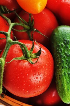 �ucumbers, red tomatoes lie in  basket photo