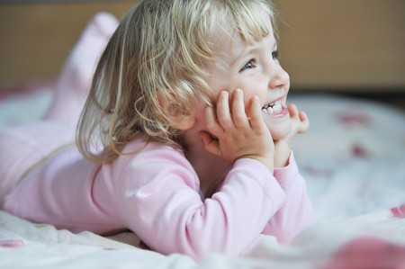 Beautiful little girl lying on bed at house photo