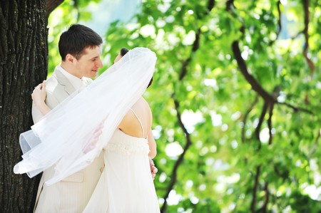 groom and bride in white dress on background of green trees