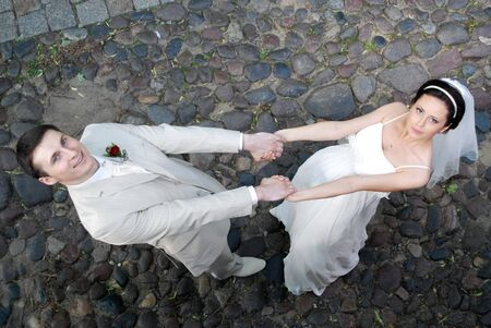 groom and  bride in  white dress dance on sidewalk photo