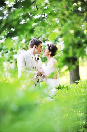 groom and bride in white dress on background of green trees Reklamní fotografie - 7543306