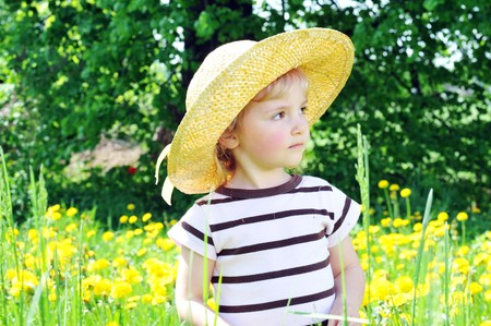 little girl in straw hat walks on  blossoming field photo